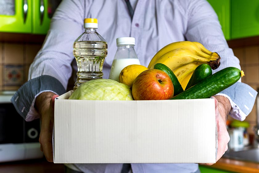 Person holding box full of fruits and vegetables